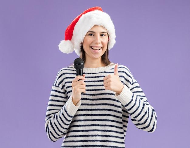サンタの帽子をかぶって笑顔の若い白人の女の子は、コピースペースと紫色の壁に分離されたマイクと親指を保持します