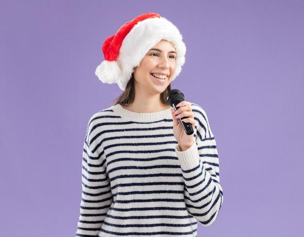 La giovane ragazza caucasica sorridente con il cappello della santa tiene il microfono che esamina il lato