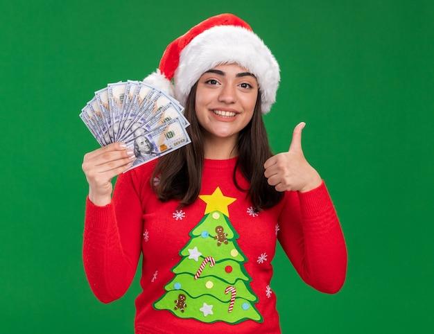 サンタの帽子と笑顔の若い白人の女の子は、コピースペースで緑の背景に分離されたお金と親指を保持します