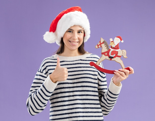 Smiling young caucasian girl with santa hat holds santa on rocking horse decoration and thumbs up isolated on purple wall with copy space