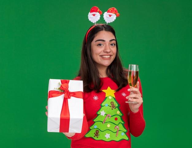 Улыбающаяся молодая кавказская девушка с ободком санта-клауса держит бокал шампанского и рождественскую подарочную коробку, изолированную на зеленом фоне с копией пространства
