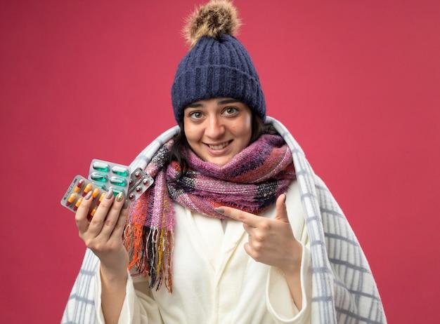 真っ赤な壁に隔離されたカプセルのパックを保持し、指している格子縞の保持に包まれたローブの冬の帽子とスカーフを身に着けている若い白人の病気の女の子を笑顔