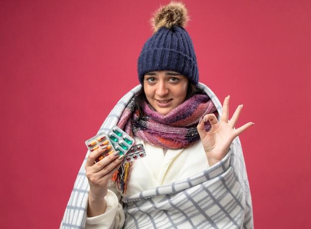 真っ赤な壁に隔離されたokサインをしているカプセルの格子縞の保持パックに包まれたローブの冬の帽子とスカーフを身に着けている若い白人の病気の女の子の笑顔