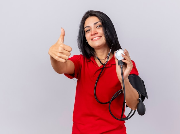 Улыбающаяся молодая кавказская больная девушка со стетоскопом смотрит в камеру, измеряет ее давление с помощью сфигмоманометра, показывая большой палец вверх изолированно на белом фоне с копией пространства