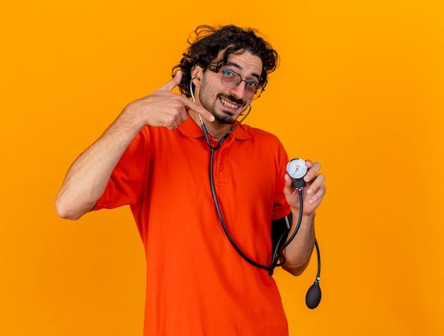 コピースペースとオレンジ色の壁に分離された血圧計を保持し、指している眼鏡と聴診器を身に着けている若い白人の病気の人の笑顔