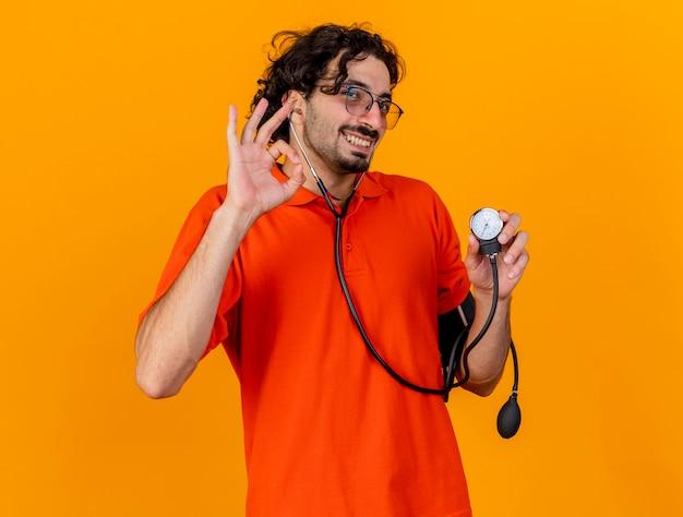 Улыбающийся молодой кавказский больной человек в очках и стетоскопе держит сфигмоманометр, делает хорошо, знак изолирован на оранжевой стене