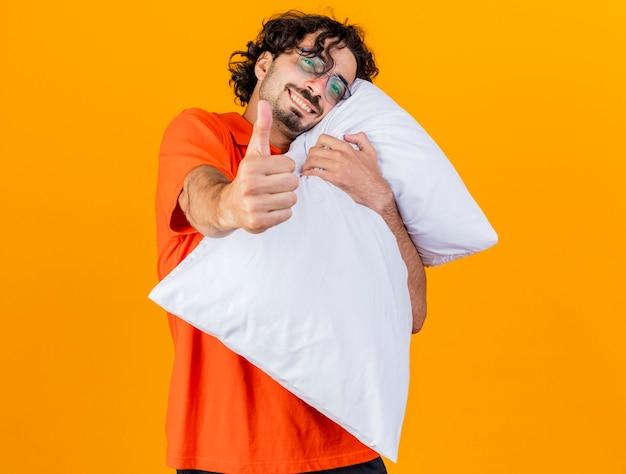 Sorridente giovane indoeuropeo uomo malato con gli occhiali abbracciando cuscino guardando la telecamera che mostra il pollice in alto isolato su sfondo arancione con copia spazio
