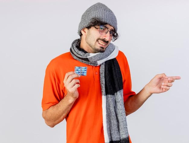 흰 벽에 고립 된 측면에서 가리키는 의료 캡슐의 팩을 들고 안경 겨울 모자와 스카프를 착용하는 젊은 백인 아픈 남자 미소