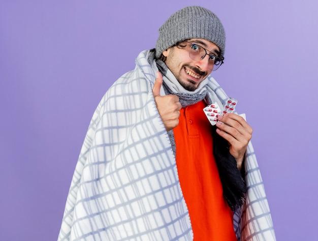 紫色の背景に分離された親指を上に表示しているカメラを見て、カプセルの格子縞の保持パックに包まれた眼鏡の冬の帽子とスカーフを身に着けている若い白人の病気の人の笑顔