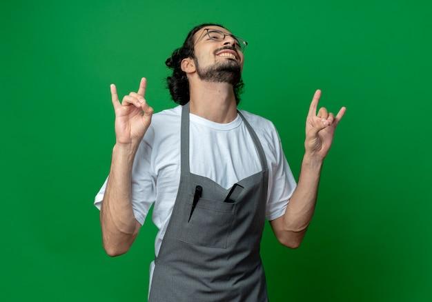 Улыбающийся молодой кавказский парикмахер в очках и с волнистой лентой для волос в униформе делает рок-знаки, выглядящие прямо