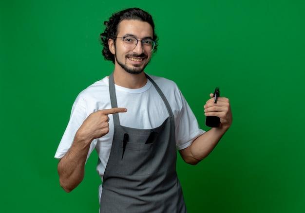 Улыбающийся молодой кавказский парикмахер в очках и с волнистой лентой для волос в униформе держит и показывает на бутылку с распылителем