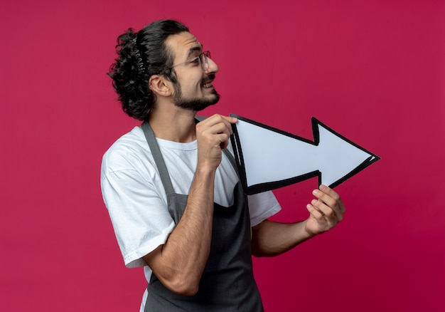 젊은 백인 남성 이발사 안경과 물결 모양의 헤어 밴드를 입고 측면에서 가리키는 화살표 표시를 들고 진홍색 배경에 고립 된 측면을보고 웃고