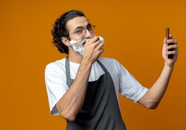 Улыбающийся молодой кавказский мужчина-парикмахер в очках и с волнистой лентой для волос в униформе держит кисть для бритья и мобильный телефон с кремом для бритья, положенный на лицо, изолированное на оранжевом фоне