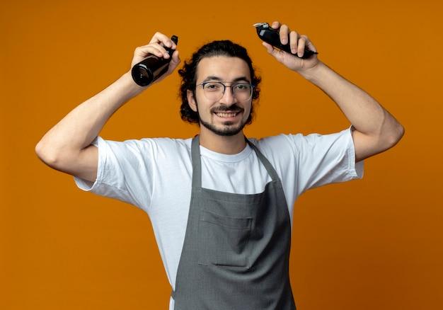Улыбающийся молодой кавказский парикмахер в очках и с волнистой лентой для волос в униформе, поднимающей спрей и машинки для стрижки волос, изолированные на оранжевом фоне