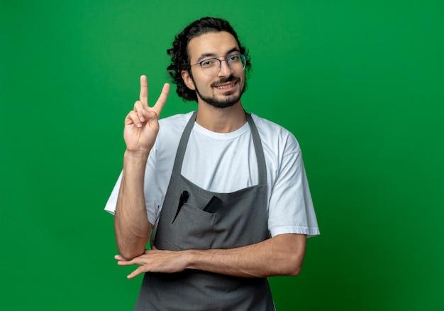 Sorridente giovane maschio caucasico barbiere con gli occhiali e fascia per capelli ondulati in uniforme facendo segno di pace e mettendo la mano sotto il gomito isolato su sfondo verde con spazio di copia