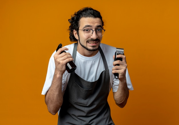 Smiling young caucasian male barber wearing glasses and wavy hair band in uniform holding spray bottle and hair clippers isolated on orange background with copy space
