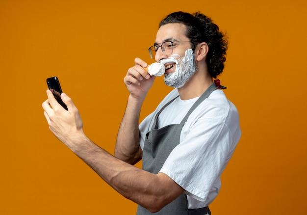 Sorridente giovane barbiere maschio caucasico con gli occhiali e fascia per capelli ondulati in uniforme tenendo il pennello da barba vicino alla bocca tenendo e guardando il telefono cellulare con crema da barba messa sul viso