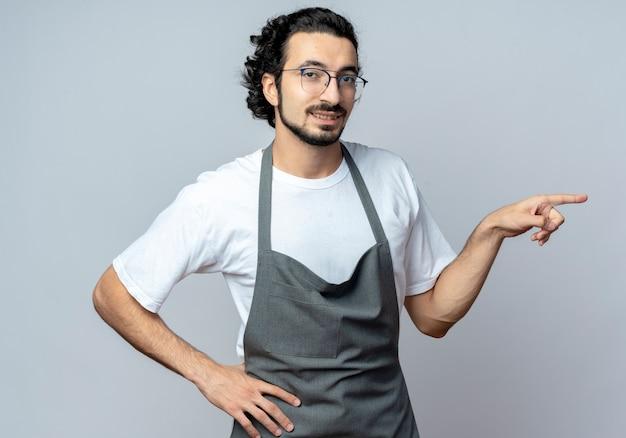 Sorridente giovane barbiere maschio caucasico con gli occhiali e fascia per capelli ondulati in uniforme mettendo la mano sulla vita e indicando il lato isolato su priorità bassa bianca