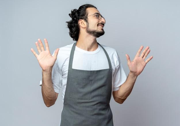 Sorridente giovane barbiere maschio caucasico con gli occhiali e fascia per capelli ondulati in uniforme che mostra le mani vuote guardando lato isolato su sfondo bianco