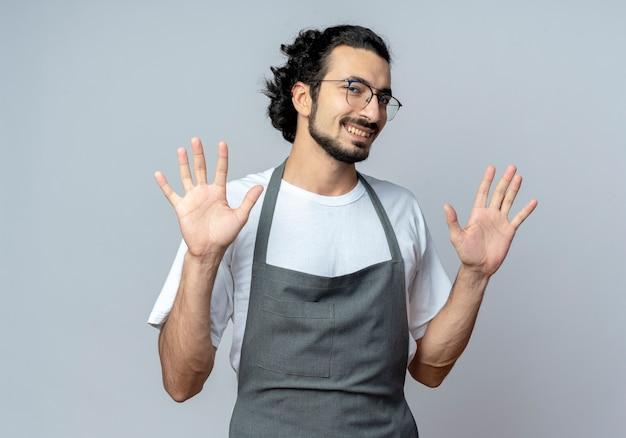Sorridente giovane maschio caucasico barbiere con gli occhiali e fascia per capelli ondulati in uniforme che mostra le mani vuote su sfondo bianco
