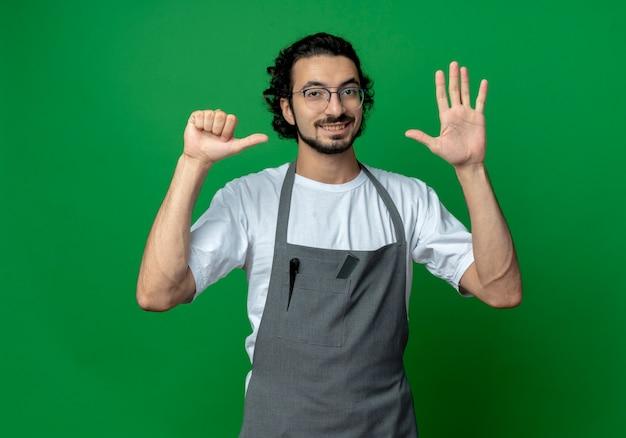 Sorridente giovane maschio caucasico barbiere con gli occhiali e fascia per capelli ondulati in uniforme che mostra sei con le mani isolate su sfondo verde con spazio di copia