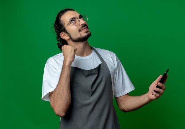젊은 백인 남성 이발사 유니폼과 안경을 쓰고 주먹을 떨리는 휴대 전화를 들고 녹색 배경에 고립 된 찾고 웃고