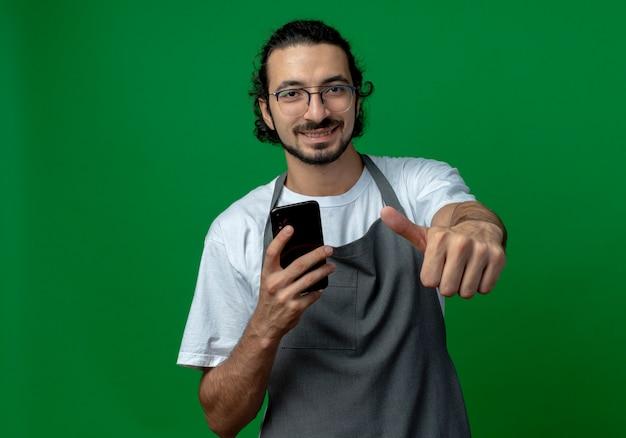 Sorridente giovane barbiere maschio caucasico indossando l'uniforme e occhiali tenendo il telefono cellulare e mostrando il pollice in alto isolato su sfondo verde con spazio di copia