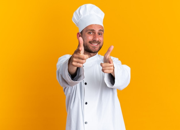 Smiling young caucasian male cook in chef uniform and cap doing pistol gesture