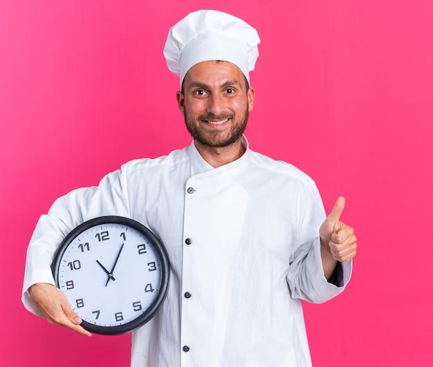 Sorridente giovane maschio caucasico cuoco in uniforme da chef e berretto che tiene l'orologio guardando la telecamera che mostra il pollice in alto isolato sul muro rosa