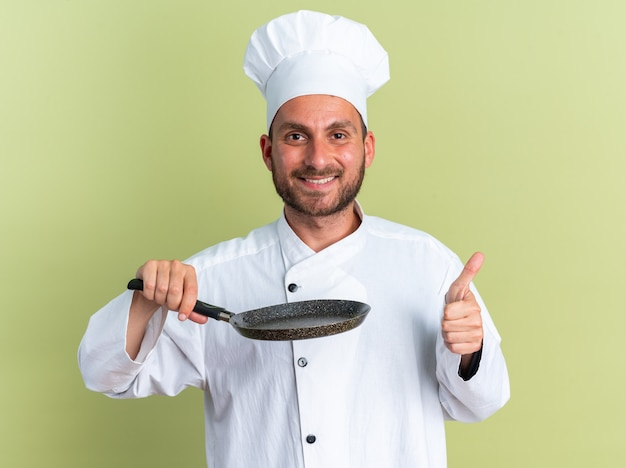 Smiling young caucasian male cook in chef uniform and cap holding frying pan looking at camera showing thumb up isolated on olive green wall
