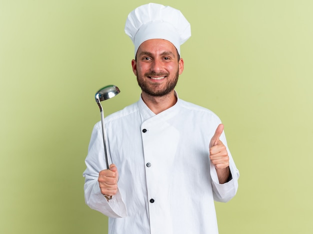 Smiling young caucasian male cook in chef uniform and cap holding ladle looking at camera showing thumb up isolated on olive green wall
