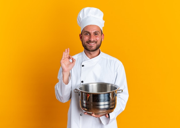 Smiling young caucasian male cook in chef uniform and cap holding pot doing ok sign