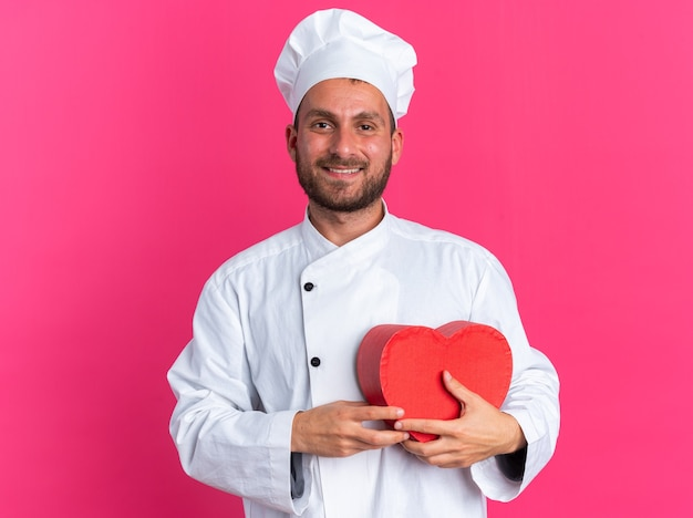요리사 유니폼을 입고 하트 모양을 들고 있는 모자를 쓰고 웃고 있는 젊은 백인 남성 요리사