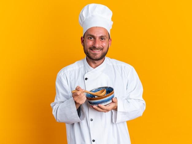 Улыбающийся молодой кавказский повар в униформе шеф-повара и кепке держит ложку и миску, глядя в камеру, изолированную на оранжевой стене
