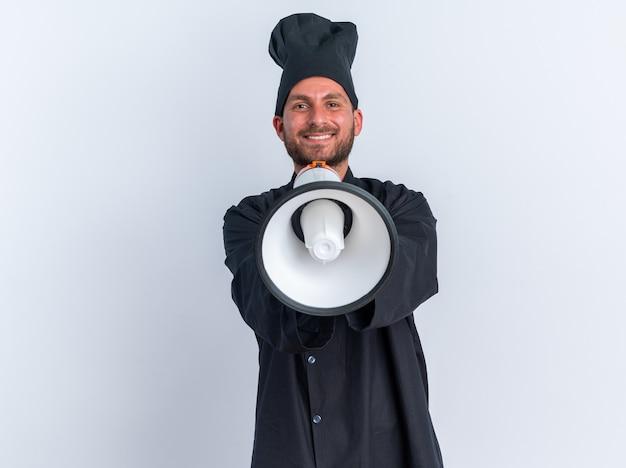 Улыбающийся молодой кавказский повар в униформе и кепке шеф-повара смотрит в камеру, протягивая динамик к камере, изолированной на белой стене с копией пространства