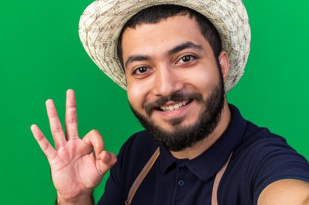 Sorridente giovane giardiniere maschio caucasico indossando il cappello da giardinaggio gesti segno ok e prendendo selfie isolato sulla parete verde con lo spazio della copia