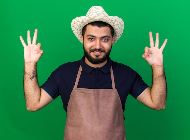 コピースペースと緑の壁に分離されたokサインを身振りで示すガーデニング帽子を身に着けている若い白人男性の庭師の笑顔