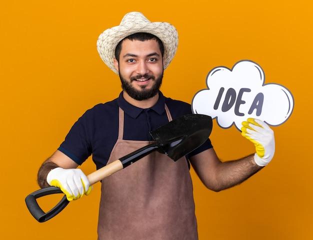 Sorridente giovane maschio caucasico giardiniere che indossa cappello e guanti da giardinaggio che tengono e puntano alla bolla di idea con vanga isolata sulla parete arancione con spazio di copia