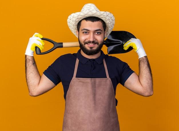 Sorridente giovane maschio caucasico giardiniere che indossa cappello da giardinaggio e guanti che tengono la vanga sul collo dietro isolato sulla parete arancione con spazio di copia