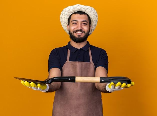 Sorridente giovane maschio caucasico giardiniere che indossa cappello e guanti da giardinaggio tenendo la vanga con due mani isolate sulla parete arancione con spazio di copia