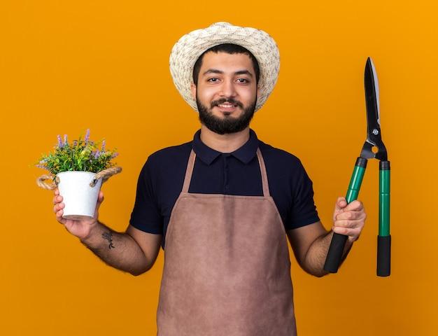 Sorridente giovane maschio caucasico giardiniere che indossa cappello da giardinaggio tenendo vaso di fiori e forbici da giardinaggio isolato sulla parete arancione con spazio di copia