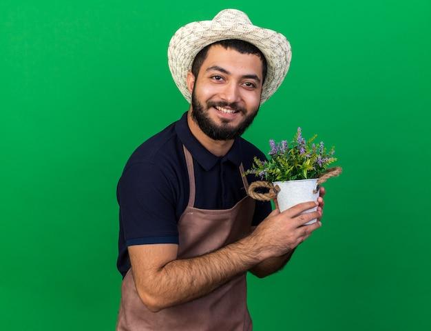 コピースペースと緑の壁に分離された植木鉢を保持しているガーデニング帽子をかぶって若い白人男性の庭師の笑顔