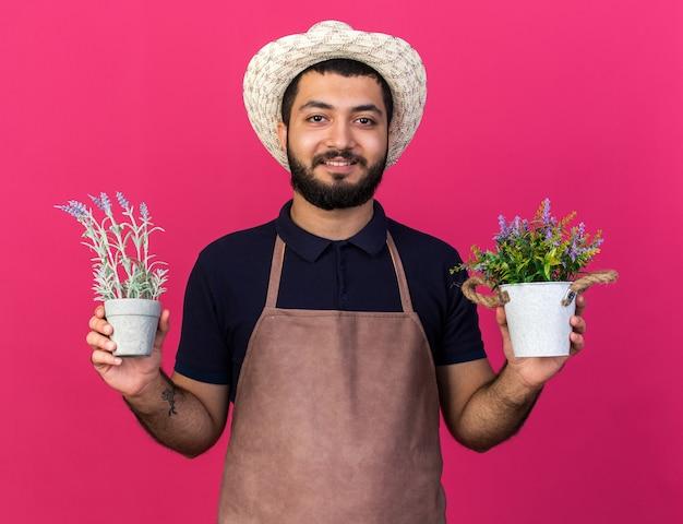 コピースペースとピンクの壁に分離された植木鉢を保持しているガーデニング帽子を身に着けている若い白人男性の庭師の笑顔