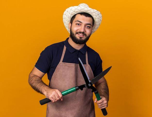 コピースペースとオレンジ色の壁に分離されたガーデニングはさみを保持しているガーデニング帽子を身に着けている若い白人男性の庭師の笑顔