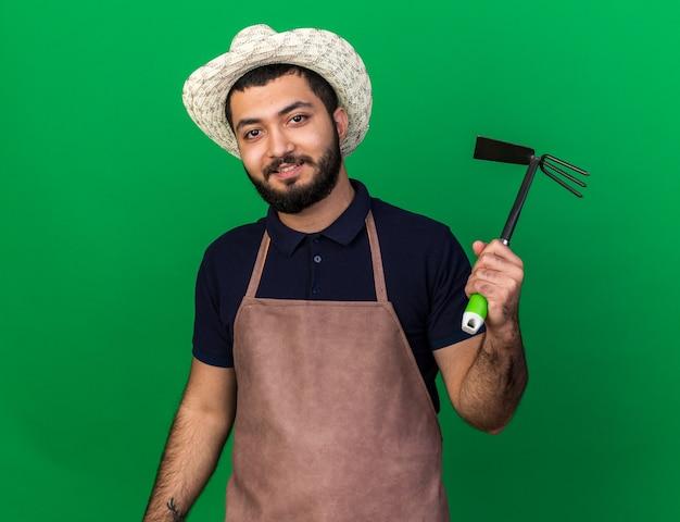 コピースペースと緑の壁に分離されたくわ熊手を保持しているガーデニング帽子を身に着けている若い白人男性の庭師