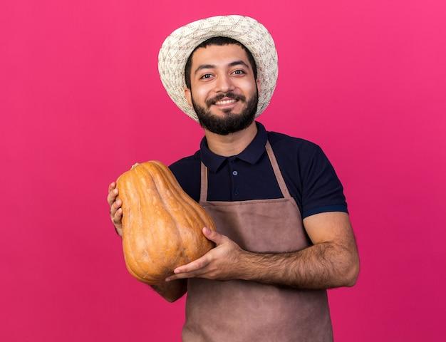 Sorridente giovane maschio caucasico giardiniere che indossa cappello da giardinaggio tenendo la zucca isolata sulla parete rosa con spazio di copia