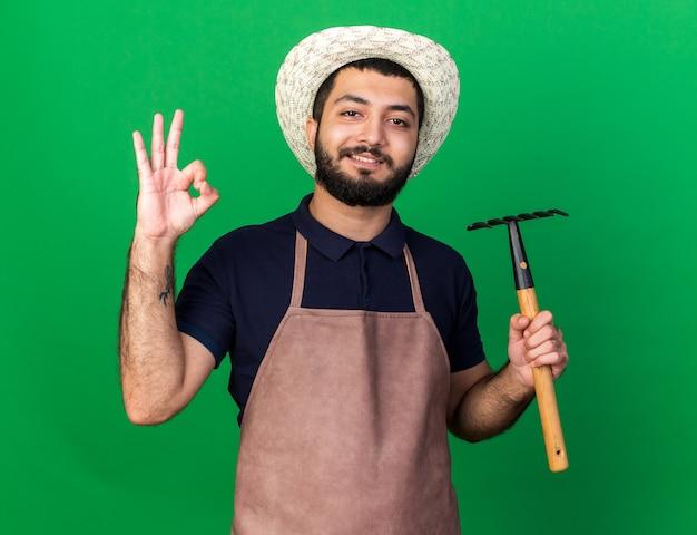 Sorridente giovane maschio caucasico giardiniere che indossa cappello da giardinaggio tenendo rastrello e gesticolando segno ok isolato sulla parete verde con spazio copia copy