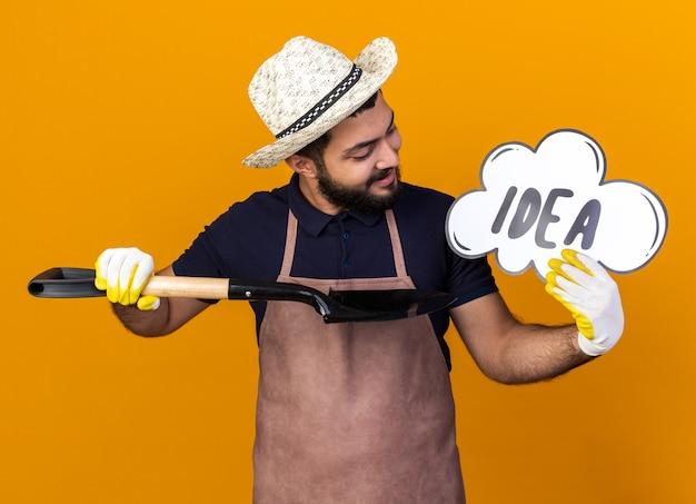 Sorridente giovane maschio caucasico giardiniere che indossa cappello da giardinaggio guardando e puntando a idea bolla con vanga isolata sulla parete arancione con spazio di copia