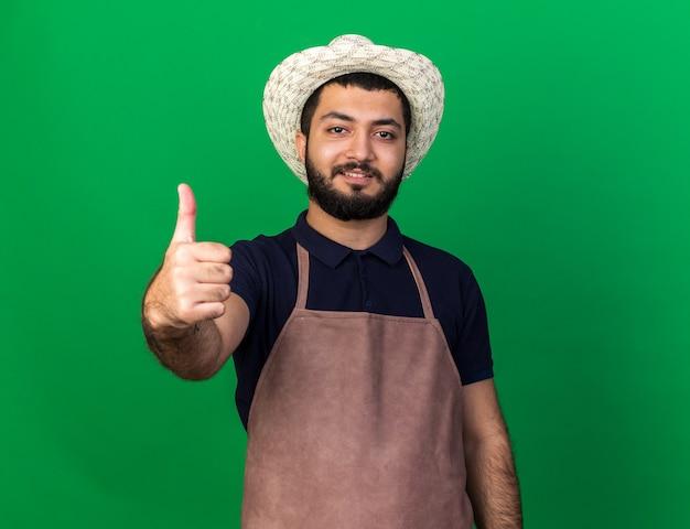 コピースペースと緑の壁に分離されたガーデニング帽子を身に着けている若い白人男性の庭師の笑顔
