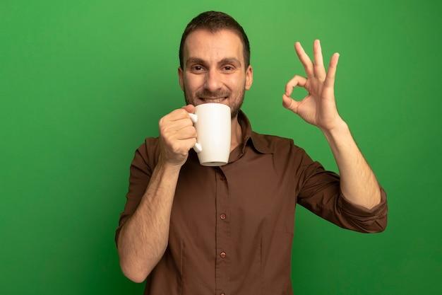 복사 공간 녹색 배경에 고립 된 확인 표시를 하 고 카메라를보고 차 한잔 들고 웃는 젊은 백인 남자